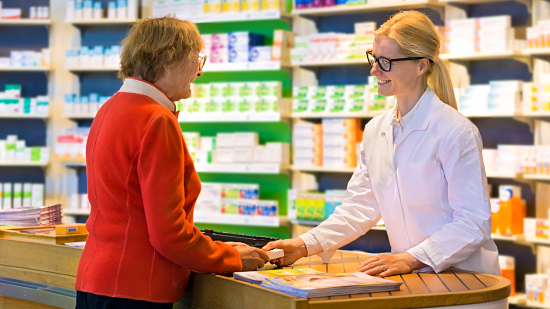 Happy senior citizen customer in red standing at pharmacy counter as pharmacist in eyeglasses and lab coat hands her a medication order.