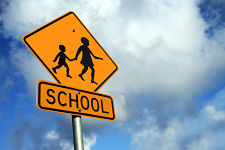 Yellow school road sign against a blue cloudy sky