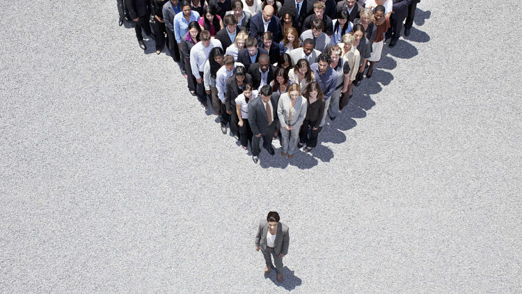 businesswoman stands in front of a crowd