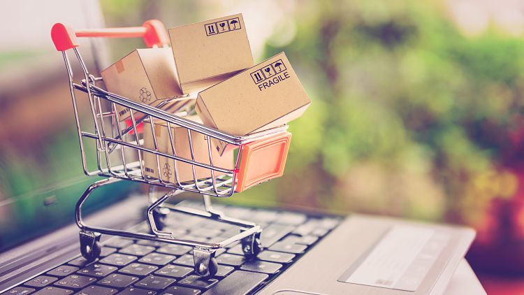 Online shopping and delivery service concept. Paper cartons in a shopping cart on a laptop keyboard