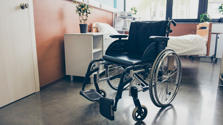 Isolated black wheel chair in the empty ward of the hospital