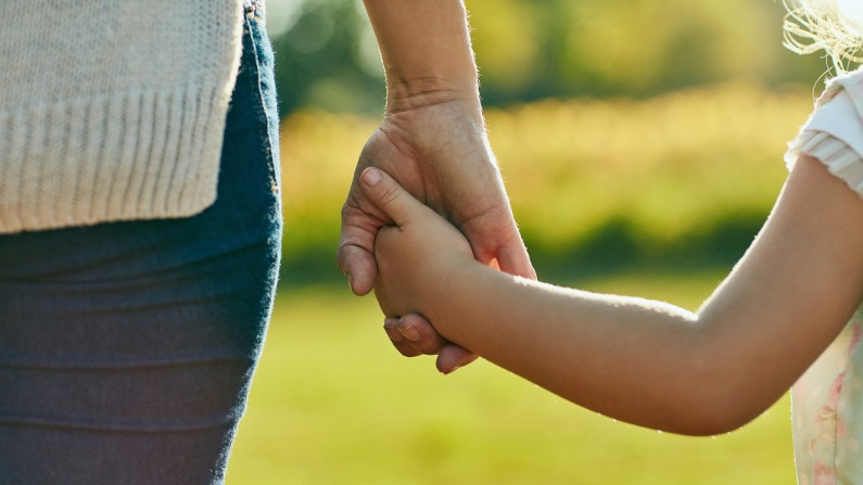 adult's hand holding child's hand