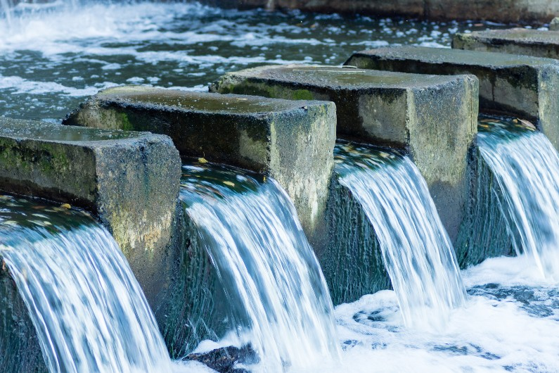 water pours through a concrete dam, for the water market